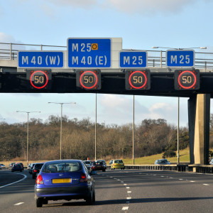 Variable speed limit signs illuminated on M25 motorway near junction with M40