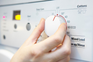 Woman Selecting Cooler Temperature On Washing Machine To Save Energy